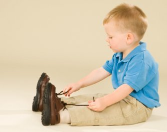 little boy thinking about tying his shoes