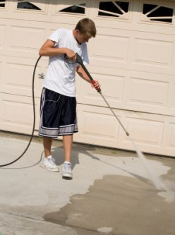 teenager power washing family driveway