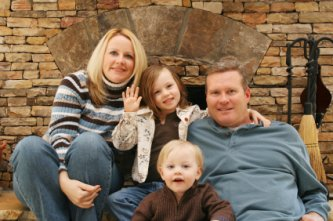 happy foster family in front of fireplace