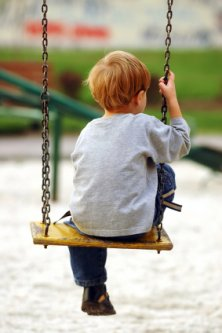 lonely preschooler swinging by himself