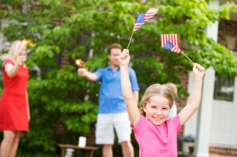 girl waving flags during a backyard 4th of July celebration