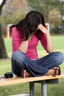 young teenager stressed out sitting along on a park bench