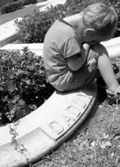 young boy crying at his Dads graveside