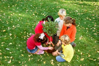 group of five children planting a tree - tips for green living and getting involved