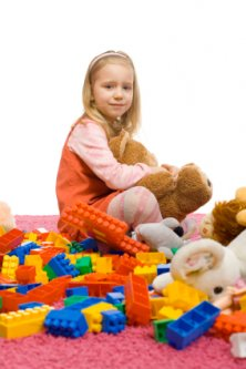 bored little girl in a mess of toys
