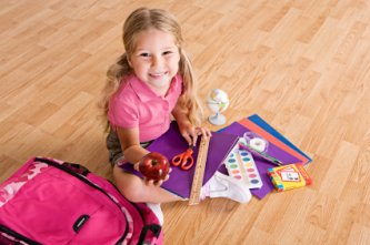 little girl with her school supplies getting ready for school