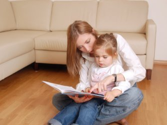 Single mom reading book to her daughter