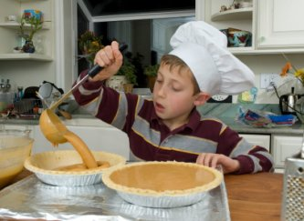 young boy helping mom make a pumpkin pie
