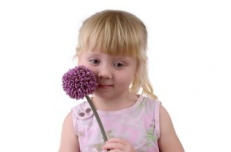 a shy child holding a flower