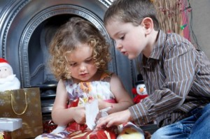 Brother helping his Little Sister Opening Her Xmas Presents